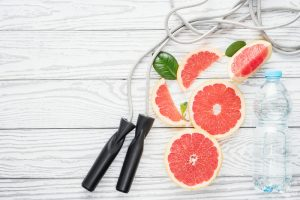 Jumping-rope, fresh grapefruits and bottle of water, on rustic white wooden table , top view, flat lay, fitness accessories. Concept of slimming, dieting and healthy nutrition.